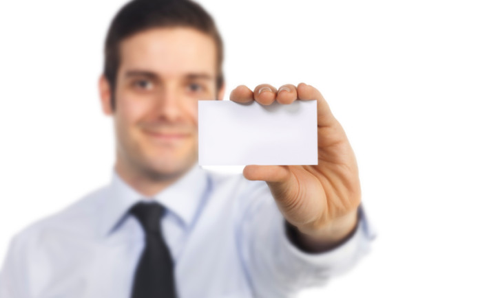 portrait of businessman showing blank card